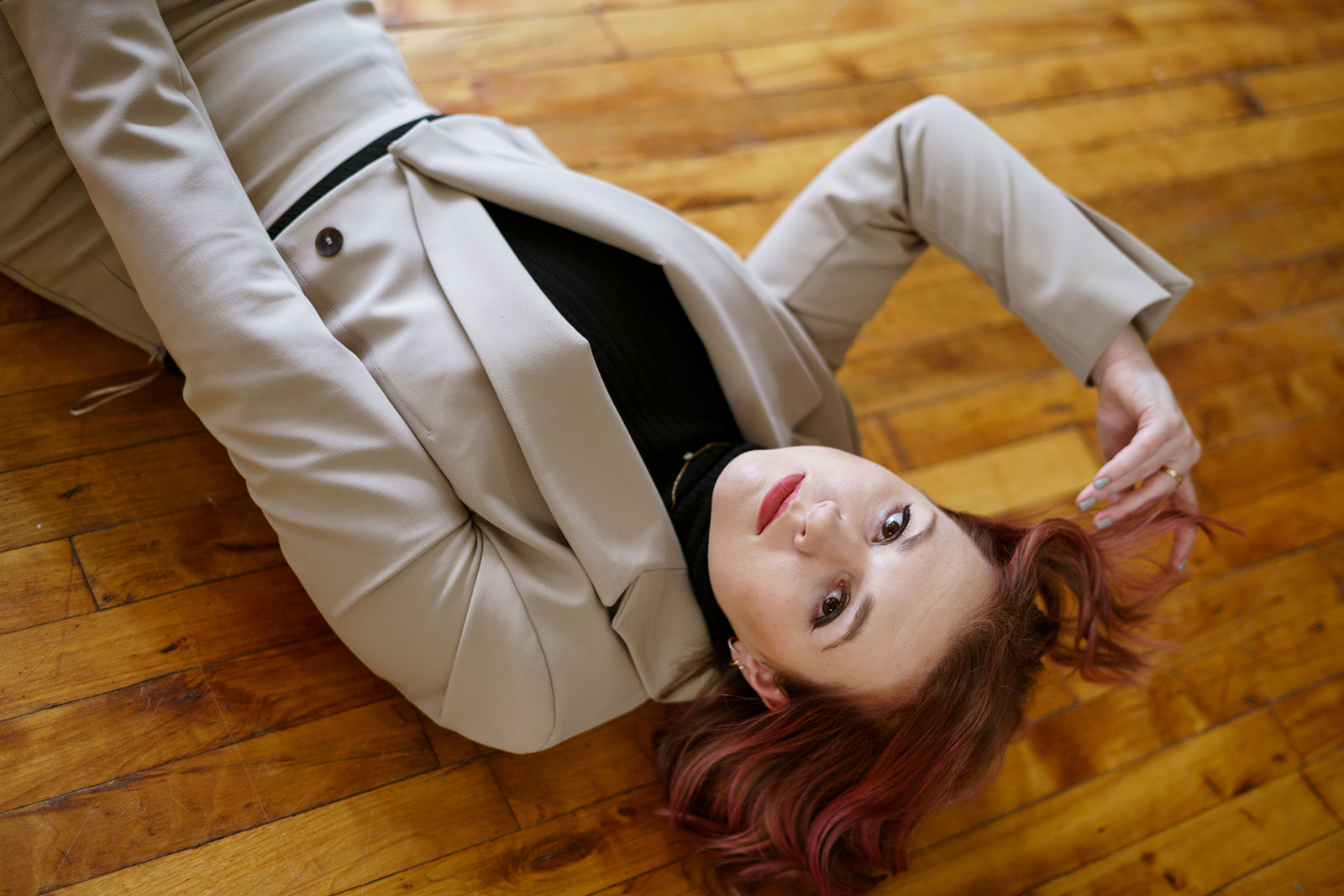 woman in tan suit laying on wood floor