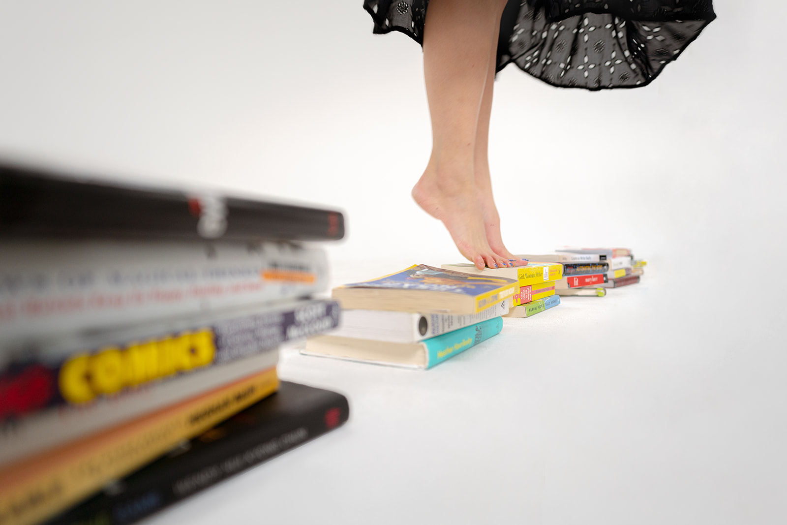 woman standing on tip toes on stack of books