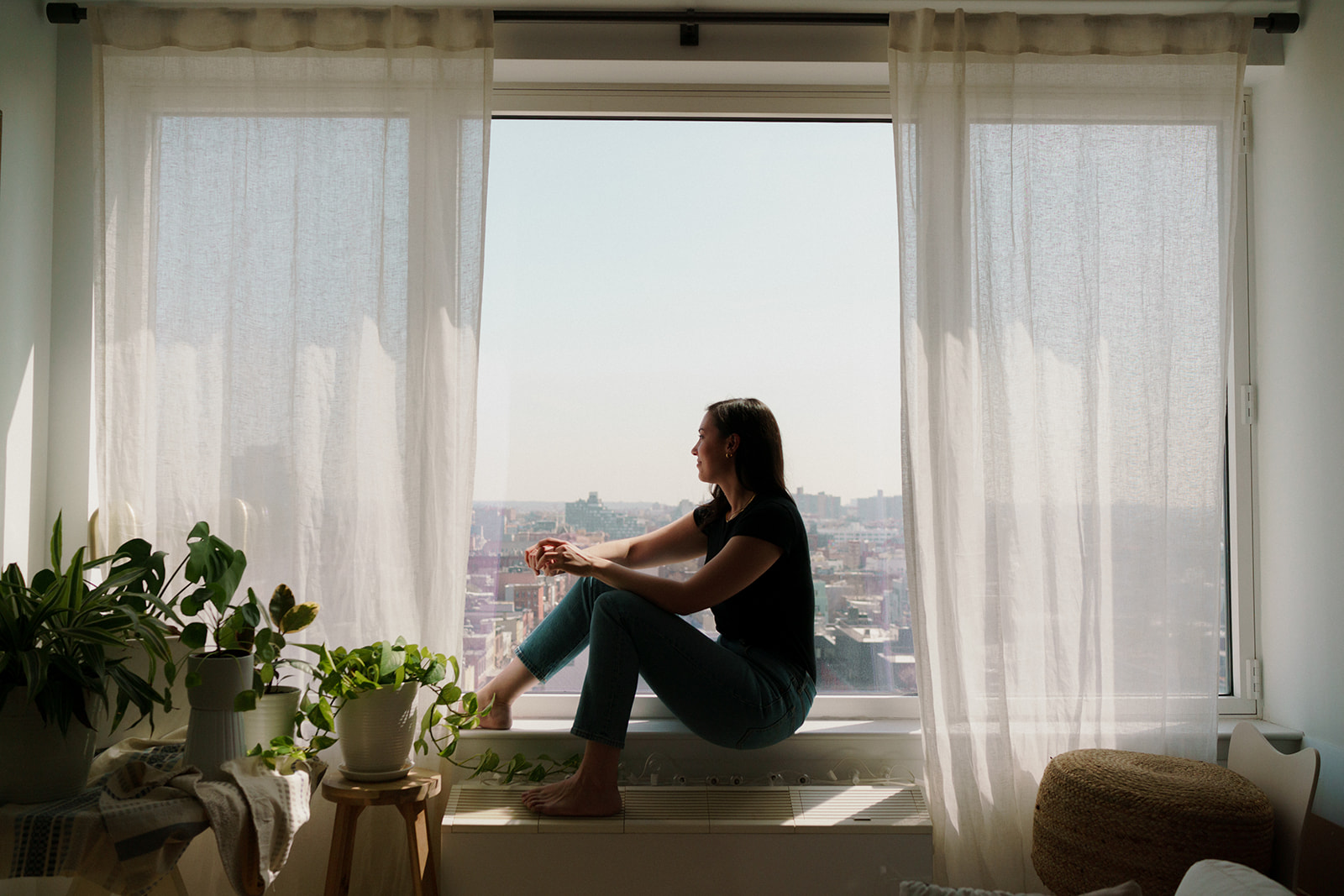 woman sitting in window sill looking at city